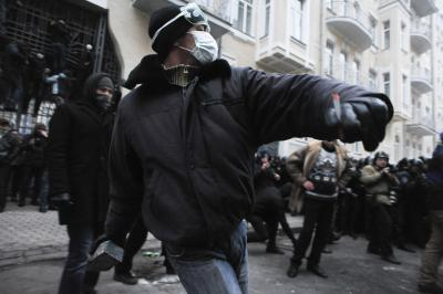 Protester throwing a piece of paving during at riot police during clashes at Bankova str Kiev Ukraine. December 1 2013